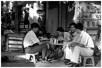 Enjoying a cafe on the streets, sitting on the typical tiny chairs. Ho Chi Minh City, Vietnam ( black and white)
