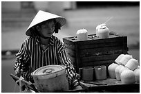 Coconut street vendor. The sweet juice is drank directly from a straw.. Ho Chi Minh City, Vietnam (black and white)
