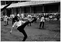 Students playing foot-only volley-ball in a school courtyard. Ho Chi Minh City, Vietnam (black and white)