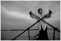 Boater using the X-shaped paddle characteristic of the Delta, sunset. Can Tho, Vietnam ( black and white)