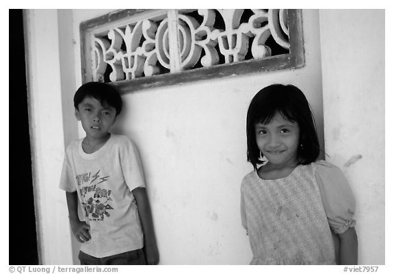 Two kids in front of a wall. Ben Tre, Vietnam (black and white)