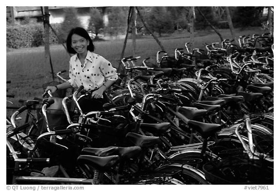 Woman retrieving her bicycle from a bicyle parking area. Mekong Delta, Vietnam (black and white)
