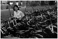Woman retrieving her bicycle from a bicyle parking area. Mekong Delta, Vietnam ( black and white)