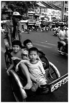 Kids sharing cyclo ride, Ho Chi Minh city. Vietnam (black and white)