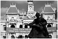 Bronze memorial to Ho Chi Minh by artist Diep Minh Chau and city hall. Ho Chi Minh City, Vietnam (black and white)