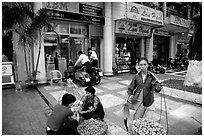Old and new: street fruit vendors and computer store. Ho Chi Minh City, Vietnam ( black and white)