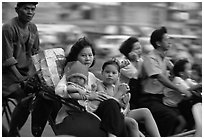 Wheels are seldom for single drivers: families on cyclo and motorbike. Ho Chi Minh City, Vietnam (black and white)