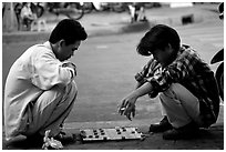 Chinese Chess game. Vietnamese people can sit on their heels for hours. Ho Chi Minh City, Vietnam ( black and white)