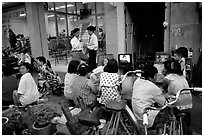 Watching TV on the street with the neighboors. Ho Chi Minh City, Vietnam ( black and white)