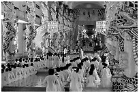 The noon ceremony, attended by priests inside the great Cao Dai temple. Tay Ninh, Vietnam ( black and white)