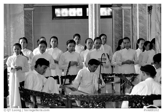 Traditional musicians during the noon ceremony. Tay Ninh, Vietnam (black and white)