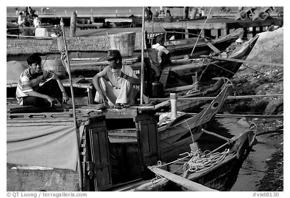 Boats from the delta waterways meet the sea. The pinapple on the pole serves to signal the boat cargo to others. Ha Tien, Vietnam (black and white)