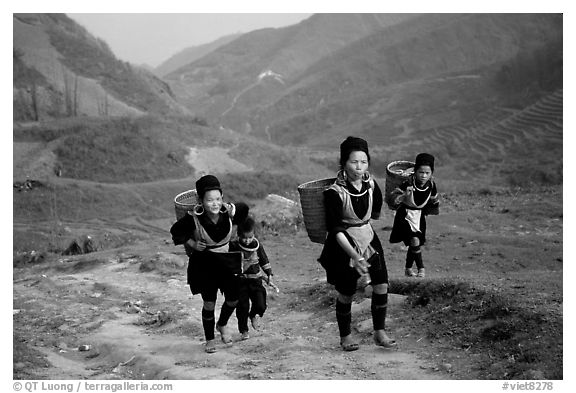 Hmong women returning to their village, which cannot be reached by the road. Sapa, Vietnam (black and white)
