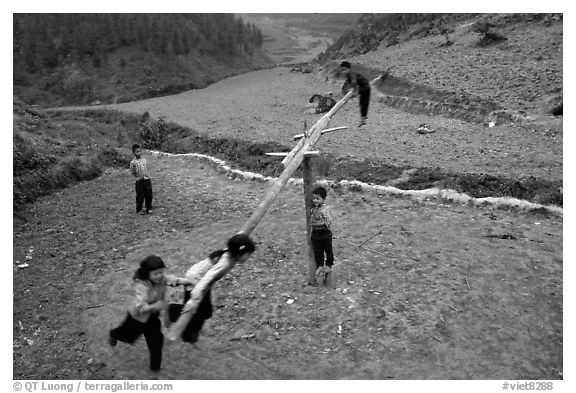 Children playing a rotating swing near Can Cau. Vietnam (black and white)