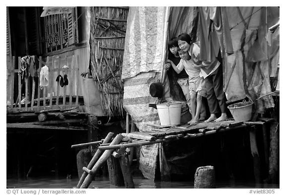 Children peering from their waterfront house. Can Tho, Vietnam