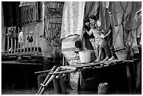 Children peering from their waterfront house. Can Tho, Vietnam (black and white)