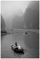 Villagers going by boat to their fields, amongst misty cliffs, Tam Coc. Ninh Binh,  Vietnam ( black and white)