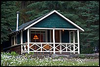 Cabin in forest with interior lights. Banff National Park, Canadian Rockies, Alberta, Canada