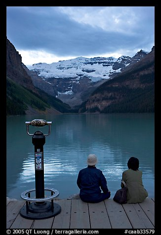 Couple sitting at the edge of Lake Louise at dawn. Banff National Park, Canadian Rockies, Alberta, Canada