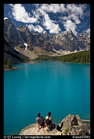 Couple sitting on the edge of Moraine Lake. Banff National Park, Canadian Rockies, Alberta, Canada