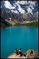 Couple sitting on the edge of Moraine Lake. Banff National Park, Canadian Rockies, Alberta, Canada (color)