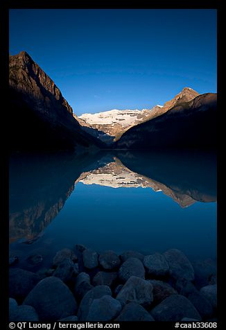 Boulders, Mirror-like Lake Louise and Victoria Peak, early morning. Banff National Park, Canadian Rockies, Alberta, Canada (color)