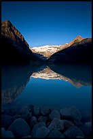 Boulders, Mirror-like Lake Louise and Victoria Peak, early morning. Banff National Park, Canadian Rockies, Alberta, Canada ( color)