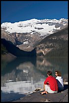 Couple sitting in the sun in front of Lake Louise, morning. Banff National Park, Canadian Rockies, Alberta, Canada (color)