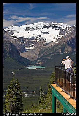 Man looking at Lake Louise through binoculars on observation platform. Banff National Park, Canadian Rockies, Alberta, Canada (color)