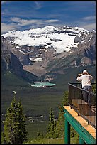 Man looking at Lake Louise through binoculars on observation platform. Banff National Park, Canadian Rockies, Alberta, Canada