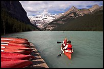 Canoeists paddling out of the boat dock in blue-green waters, Lake Louise, morning. Banff National Park, Canadian Rockies, Alberta, Canada
