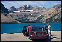Tourists stepping out of a car next to Bow Lake. Banff National Park, Canadian Rockies, Alberta, Canada (color)