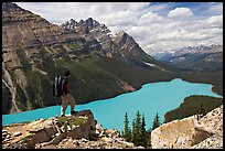 Hiker standing on a rock overlooking Peyto Lake. Banff National Park, Canadian Rockies, Alberta, Canada (color)