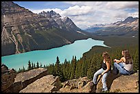 Visitors sitting on a rook overlooking Peyto Lake. Banff National Park, Canadian Rockies, Alberta, Canada (color)