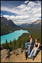 Women sitting on a rook overlooking Peyto Lake. Banff National Park, Canadian Rockies, Alberta, Canada (color)