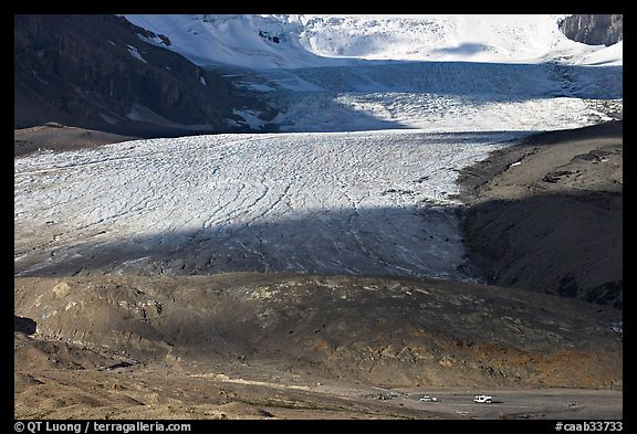 Base of Athabasca Glacier with cars parked on lot. Jasper National Park, Canadian Rockies, Alberta, Canada