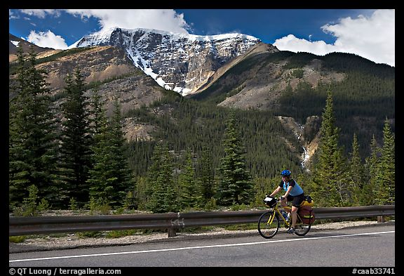 Woman cycling the Icefields Parkway. Jasper National Park, Canadian Rockies, Alberta, Canada (color)