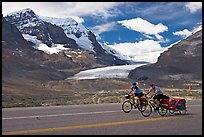 Cyclists on the Icefields Parkway in front of the Athabasca Glacier. Jasper National Park, Canadian Rockies, Alberta, Canada (color)