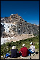 Hikers sitting in front of Mt Edith Cavell next to trail. Jasper National Park, Canadian Rockies, Alberta, Canada