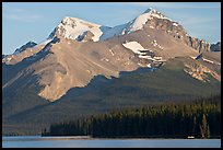 Canoe dwarfed by the Mt Charlton and Mt Unwin surrounding Maligne Lake. Jasper National Park, Canadian Rockies, Alberta, Canada