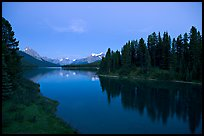 Maligne River outlet, row of evergreens, and  Maligne River, blue dusk. Jasper National Park, Canadian Rockies, Alberta, Canada