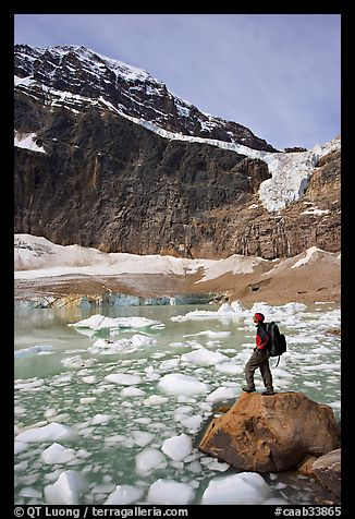 Hiker with backpack looking at iceberg-filed lake, glaciers, and mountain, Mt Edith Cavell. Jasper National Park, Canadian Rockies, Alberta, Canada (color)