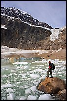 Hiker with backpack looking at iceberg-filed lake, glaciers, and mountain, Mt Edith Cavell. Jasper National Park, Canadian Rockies, Alberta, Canada