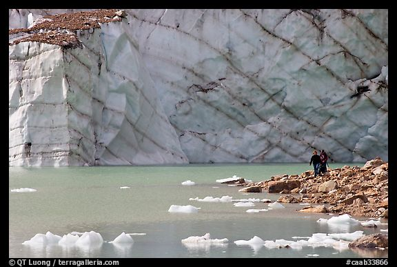 Hikers on the shore of Cavell Pond with high glacier wall behind. Jasper National Park, Canadian Rockies, Alberta, Canada