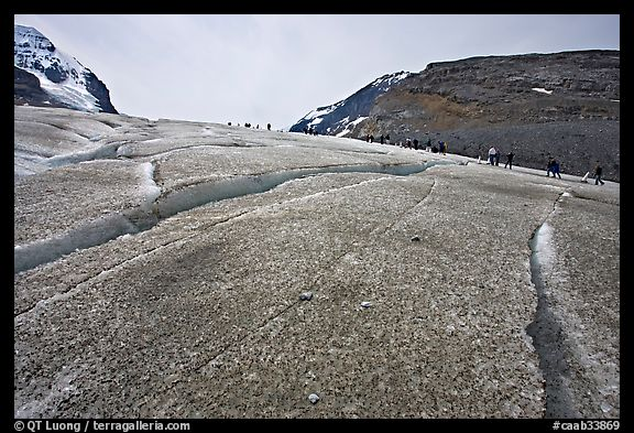 Crevasses on Athabasca Glacier with a line of tourists in the background. Jasper National Park, Canadian Rockies, Alberta, Canada