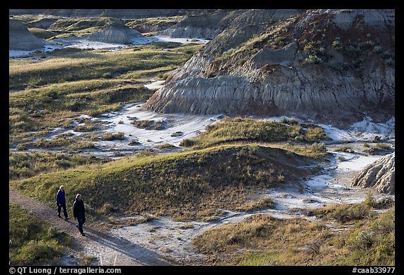 Hikers amongst badlands, morning, Dinosaur Provincial Park. Alberta, Canada (color)