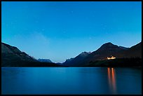 Waterton lake by night with stars in the sky in lights of Price of Wales Hotel. Waterton Lakes National Park, Alberta, Canada