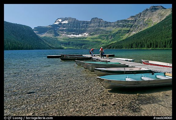 Fishermen walking on dock after unloading a canoe, Cameron Lake. Waterton Lakes National Park, Alberta, Canada