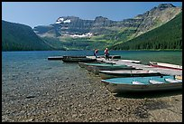 Fishermen walking on dock after unloading a canoe, Cameron Lake. Waterton Lakes National Park, Alberta, Canada ( color)