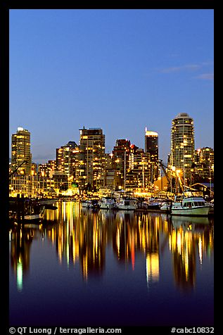 Fishing boats and skyline light reflected at night. Vancouver, British Columbia, Canada (color)